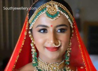 bride in polki emerald jewelelry set